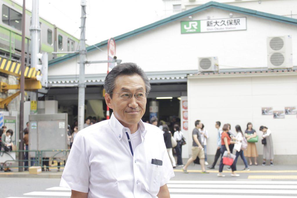 [新大久保駅前でポーズをとる阿部さん]